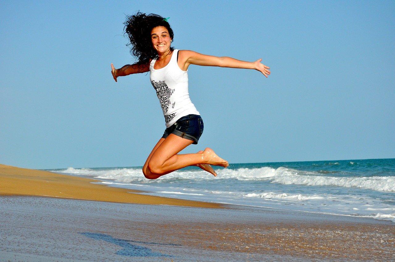 jeune femme souriante qui saute sur une plage